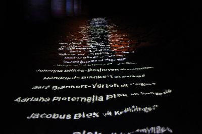 Names of victims projected on the sand.